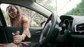 Busty latina gives a guy handjob through car...