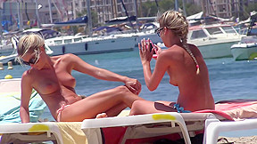 Two hot bodied blondes sunbathe beach...