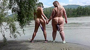 Lesbians nudists walk along the river bank with...