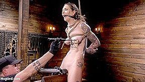 Is dominated in grueling bondage hogtied...