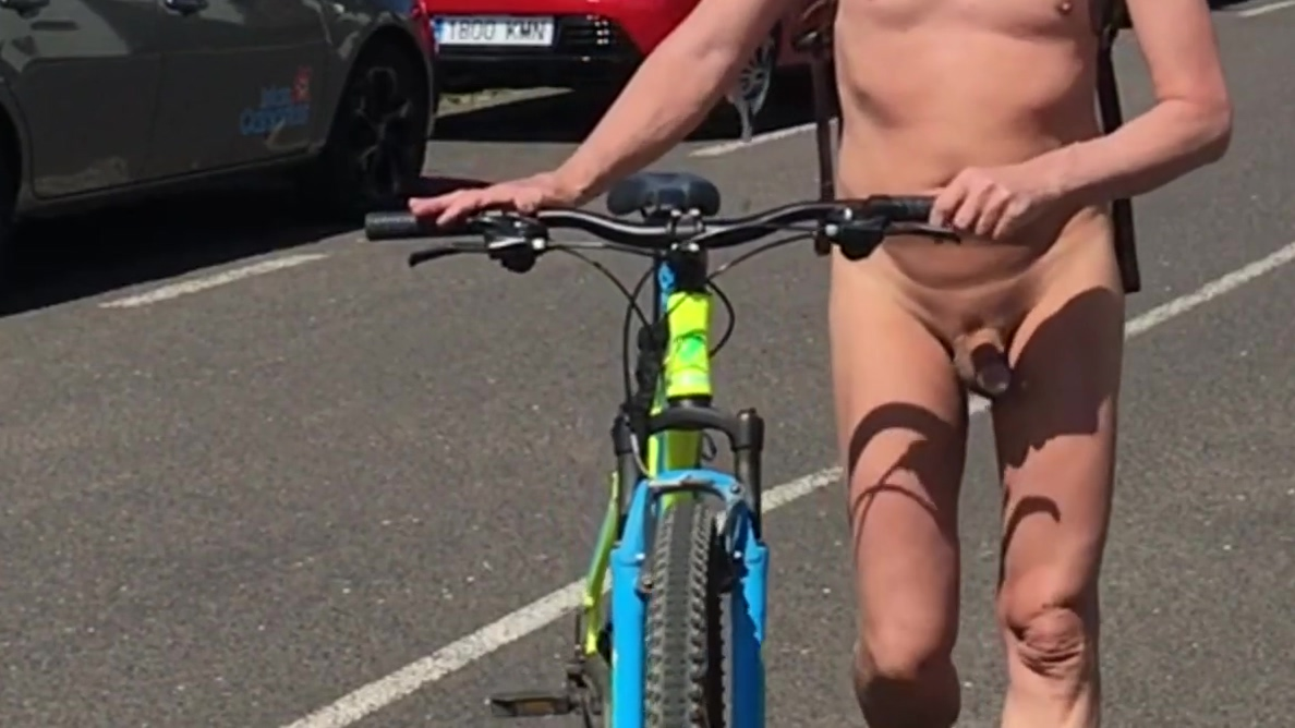 Naked on a bicycle through a town side boob no bra