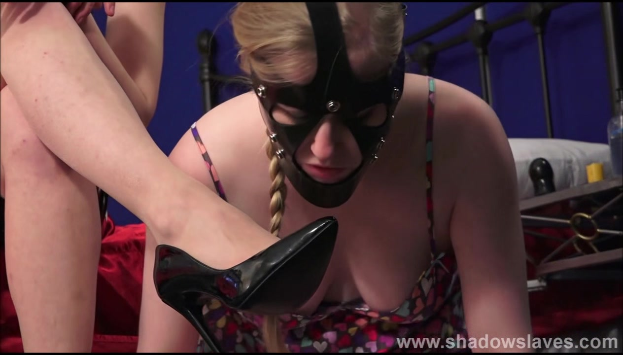 Satine Spark bizarre lesbian bondage and lezdom humiliation of boot licking blonde leather masked submissive in bedroom